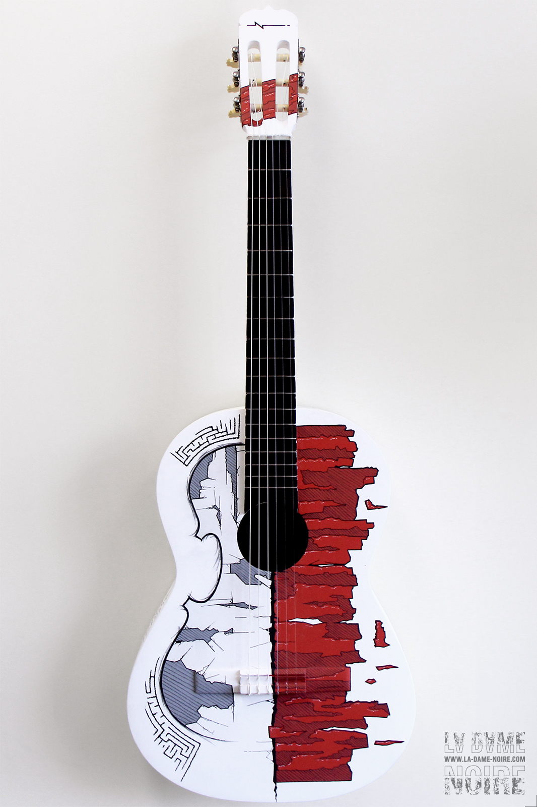 Front side of an acoustic guitar painted in white with the shape of a violin drawed on it